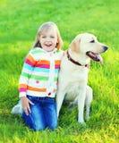 Glückliches Kind mit labrador retriever-Hund auf Gras Stockfotos