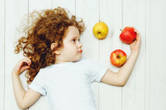 Glückliches Kind mit roten Äpfeln auf hellem Bretterboden lizenzfreie stockfotos