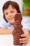 Glückliches Kind mit SchokoladenOsterhasen Stockfotos