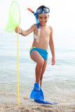 Glückliches Kind mit Tauchausrüstung auf dem Strand Stockbild