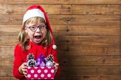 Glückliches Kind in Sankt-Hut, der einen Kasten mit Weihnachtsbällen auf a hält Stockfoto