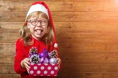 Glückliches Kind in Sankt-Hut, der einen Kasten mit Weihnachtsbällen auf a hält Lizenzfreie Stockfotografie