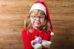 Glückliches Kind in Sankt-Hut hält Weihnachtsball auf einem hölzernen backgr Stockfotografie