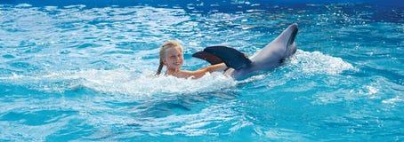Glückliches Kind und Delphine im blauen Wasser Stockfotos