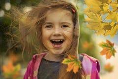 Glückliches Kind und Herbstblätter Lizenzfreie Stockfotos