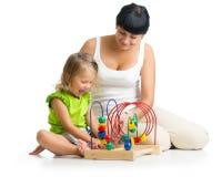 Glückliches Kind und Mutter, die mit dem pädagogischen Spielzeug lokalisiert spielt stockfotos