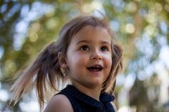 Glückliches Kindergesicht mit dem blonden Haar, den braunen eys und bokeh Hintergrund stockfotos