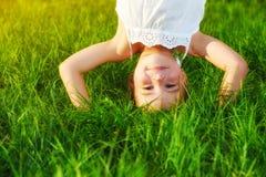 Glückliches Kindermädchen, das auf seinem Kopf auf Gras in SU umgedreht steht Lizenzfreie Stockfotografie