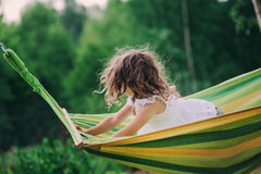 Glückliches Kindermädchen, das in der Hängematte auf Sommerlager in den Waldsaisontätigkeiten im Freien sich entspannt Lizenzfreie Stockfotos
