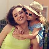 Glückliches Kindermädchen, das draußen ihren lächelnden Muttersommer umfasst Stockfoto