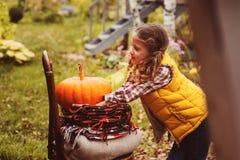 Glückliches Kindermädchen, das frische Kürbise auf dem Bauernhof auswählt stockfotografie