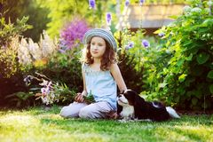 Glückliches Kindermädchen, das im Sommergarten mit ihrem Spanielhund sich entspannt Stockfotografie