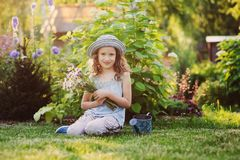Glückliches Kindermädchen, das kleinen Gärtner im Sommer, in tragendem lustigem Hut spielt und Blumenstrauß hält Lizenzfreies Stockfoto