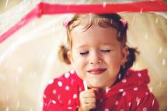 Glückliches Kindermädchen, das mit einem Regenschirm im Regen lacht Stockbild