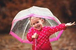Glückliches Kindermädchen, das mit einem Regenschirm im Regen lacht Lizenzfreies Stockbild