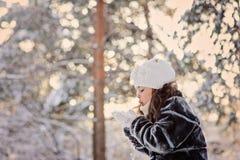 Glückliches Kindermädchen, das Spaß im schneebedeckten Wald des Winters hat lizenzfreie stockfotografie