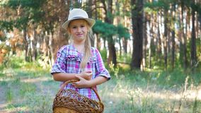 Glückliches Kindermädchen, das wilde Pilze auf dem Weg kleinen Mädchen im Sommer- oder Herbstdes wald A mit einem Korb und Pilzen stock footage
