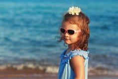 Glückliches Kindermädchen in den Sonnenbrillen auf blauem Seehintergrund Lizenzfreies Stockfoto