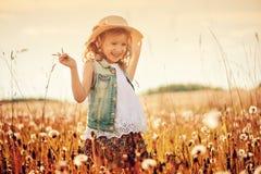 Glückliches Kindermädchen im Stroh, das mit Schlagbällen auf Sommerfeld spielt Lizenzfreies Stockbild