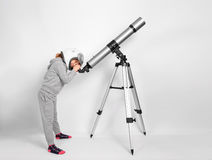 Glückliches Kindermädchen kleidete in den Blicken eines Astronautenkostüms durch ein großes Teleskop an Lizenzfreie Stockfotografie