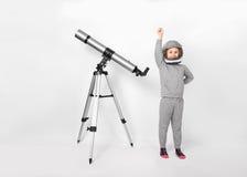 Glückliches Kindermädchen kleidete in einem Astronautenkostüm an, das neben dem Teleskop steht lizenzfreies stockfoto