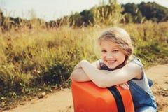 Glückliches Kindermädchen mit dem orange Koffer, der allein auf Sommerferien reist Kind, das zum Sommerlager geht Stockfotos