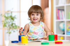 Glückliches Kindermädchen mit den Händen malte Farbfarben Lizenzfreie Stockfotografie