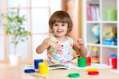 Glückliches Kindermädchen mit den Händen malte Farbfarben Lizenzfreie Stockbilder