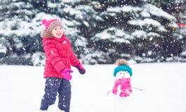 Glückliches Kindermädchen mit einem Schneemann auf einem Winterweg Lizenzfreie Stockfotos