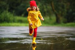 Glückliches Kindermädchen mit Gummistiefeln läuft in Pfütze auf dem wal Herbst stockbilder
