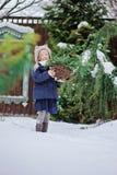 Glückliches Kindermädchen spielt im schneebedeckten Garten des Winters Stockfotos