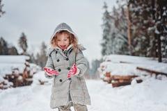Glückliches Kindermädchen spielt im schneebedeckten Wald des Winters mit Baumholzschlag auf Hintergrund Stockbilder