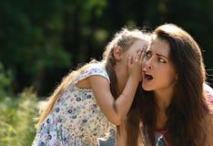 Glückliches Kindermädchen, welches das Geheimnis zu ihrem überraschenden entsetzten m flüstert Lizenzfreie Stockfotos