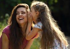Glückliches Kindermädchen, welches das Geheimnis zu ihrem lachenden jungen mothe flüstert Lizenzfreie Stockfotografie