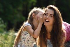 Glückliches Kindermädchen, welches das Geheimnis zu ihrem lachenden jungen mothe flüstert Lizenzfreies Stockfoto