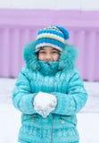 Glückliches Kindermädchenkind draußen im Winter, der mit Schnee spielt Stockfoto