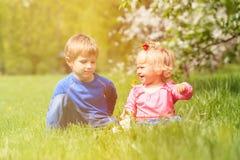 Glückliches Kinderspiel mit Frühlingsblumen Lizenzfreie Stockfotos