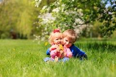 Glückliches Kinderspiel mit Frühlingsblumen Stockfotos