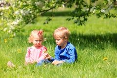 Glückliches Kinderspiel mit Frühlingsblumen Lizenzfreies Stockbild
