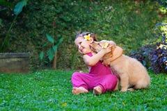 Glückliches Kinderspiel- und Umarmungsfamilienhaustier - Labrador-Welpe stockfotos