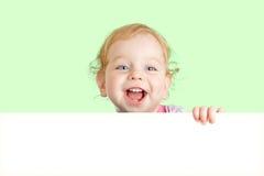 Glückliches Kindgesicht hinter unbelegter bekanntmachender Fahne lizenzfreies stockbild