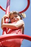 Glückliches Kindmädchen, das Spaß auf Spielplatz hat Stockfoto
