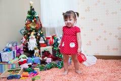 Glückliches kleine Kindweihnachten mit Weihnachtsgeschenk - eine rote Uhr herein Stockfoto