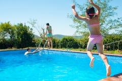 Glückliches kleines aktives Mädchen, das in Swimmingpool duri im Freien springt stockbild
