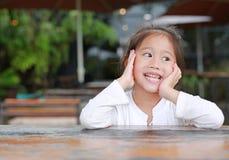 Glückliches kleines asiatisches Kindermädchen, das auf dem Holztisch liegt stockbilder