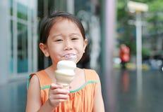 Glückliches kleines asiatisches Kindermädchen genießen, Eistüte mit befleckt um ihren Mund zu essen stockbilder
