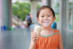 Glückliches kleines asiatisches Kindermädchen genießen, Eistüte mit befleckt um ihren Mund zu essen stockfoto
