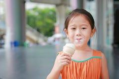 Glückliches kleines asiatisches Kindermädchen genießen, Eistüte mit befleckt um ihren Mund zu essen stockfotografie