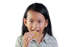 Glückliches kleines asiatisches Mädchen, das Keks isst Lizenzfreies Stockfoto