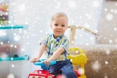 Glückliches kleines Baby, das zu Hause Fahrt-auf Auto fährt Stockfotografie